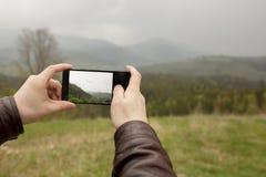 Touristisches nehmendes Bild des jungen Mannes des Waldes und der Berge auf MO Lizenzfreie Stockfotografie