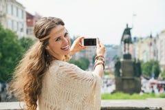 Touristisches nehmendes Foto der modischen Hippiefrau auf Mobile in Prag Stockbild