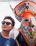 Touristisches nehmendes Foto mit buntem Maskenausführendem in Phi Ta Kon Lizenzfreies Stockfoto