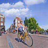 Touristisches ona-Mietfahrrad genießt Amsterdam, die Niederlande lizenzfreie stockfotos
