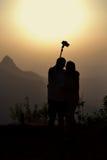 Touristisches Paar nimmt ein selfie bei Sonnenuntergang in den Hügeln Stockfotos