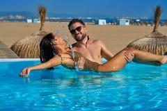 Touristisches Paarbad im Unendlichkeitspool auf einem Strand Stockbild