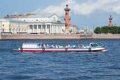 Touristisches peasure Boot mit Touristen schwimmt auf den Hintergrund des Spuckens von Vasilyevsky-Insel St Petersburg Stockfotos