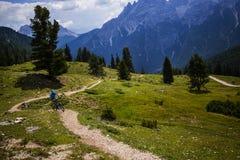 Touristisches Radfahren in Cortina d'Ampezzo, erstaunliche felsige Berge auf dem Hintergrund Mann, der MTB-enduro Flussspur reite stockfotos