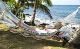 Touristisches schlafendes in der Hängematte durch das karibische Meer Lizenzfreie Stockfotos