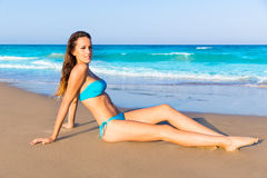 Touristisches Sitzen des Brunette beim Strandsandbräunen glücklich Stockfoto