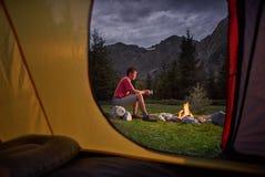 Touristisches Zelt der Innenansicht bei Sonnenuntergang Alleintourist, Mannwanderer, der am Feuer sitzt stockfotos