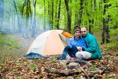 Tourists. Two tourists sit at a tent near a fire stock images