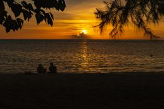 Tourists admire sunset from island beach. stock images
