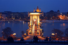 Tourists admiring the Chain Bridge. Tourists admiring the brightly lit Chain Bridge in downtown Budapest Stock Images