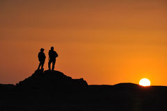 Tourists against sunset. Silhouette of two tourists against amber colored sunset. The photo was taken in the Dunhuang Yadan National Geologic Park,Dunhuang Royalty Free Stock Photography
