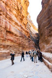 Tourists in Al Siq pass to ancient Petra town Royalty Free Stock Photo