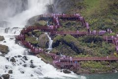 Tourists at the American Falls, United States. Tourists climbing the stairs down to the Waterfalls viewing platform and getting wet. American Falls at the royalty free stock images