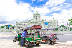 Tourists in The Ananta Samakhom Throne Hall. BANGKOK, THAILAND - August 5, 2015: Three wheeled tuk-tuk taxi cruising along touristy at The Ananta Samakhom stock photo