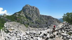Tourists in ancient theatre at Termessos, huge mountain as a background royalty free stock photos