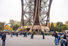 Tourists approaching the Eiffel Tower, Paris, France along a pedestrian walkway lined with autumn trees in a travel concept Royalty Free Stock Photo
