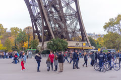 Tourists approaching the Eiffel Tower, Paris, France along a pedestrian walkway lined with autumn trees in a travel concept Stock Photography