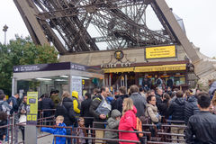 Tourists approaching the Eiffel Tower, Paris, France along a pedestrian walkway lined with autumn trees in a travel concept Royalty Free Stock Image