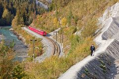 Tourists approaching Isla and observing passing by Glacier Express royalty free stock photos