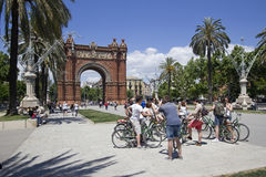 Tourists at Arc de Triomf in Barcelona. Barcelona, Spain - May 23, 2015: Tourists on bicylces take pictures in front of the Arc de Triomf triumphal arch in Royalty Free Stock Photo