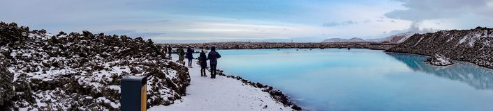Tourists At The Area Of The Blue Lagoon Watching The Blue And Milky Water With Snow Covered Mountains In The Background stock photo