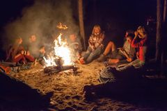 Tourists around the campfire at night. Stock Photos