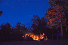 Tourists around the campfire at night. Stock Photos