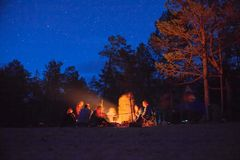 Tourists around the campfire at night. stock image