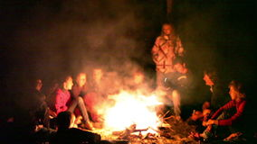 Tourists around the campfire at night. stock video footage