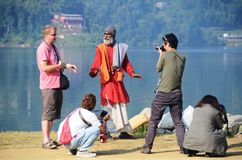 Tourists around a snake charmer in Nepal. Snake charmer performs on the shores of Phewa lake in Pokhara, Nepal Royalty Free Stock Photography