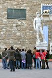 Tourists and art in Florence, Italy. Tourists admiring art in Florence, Italy. crowded urban city center with the statue of David by Michelangelo. tourism Stock Images