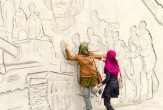 Tourists from Asia pose in front of figures describing feats of Royalty Free Stock Images