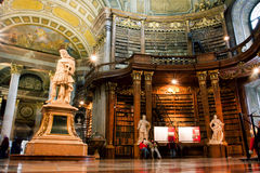 Tourists of the Austrian National Library admire the luxurious interior. Tourists and the visitors of the Austrian National Library admire the luxurious interior royalty free stock photo
