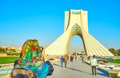 Tourists at Azadi Square in Tehran. TEHRAN, IRAN - OCTOBER 24, 2017: The young tourist makes a picture of Azadi Tower with Tehran city on the background, on stock photography