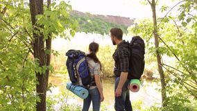 Tourists with backpacks admire view of mountains. Two hikers stand on the top of a mountain and enjoy valley view. Portrait of hikers with backpacks in the stock video footage