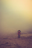 Tourists with backpacks climb to the top of the mountain in fog. Filtered image:cross processed vintage effect Stock Image