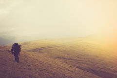 Tourists with backpacks climb to the top of the mountain in fog. Royalty Free Stock Image