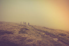 Tourists with backpacks climb to the top of the mountain in fog. Stock Images