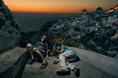 Tourists with backpacks sleeping at the Oia village Stock Photo
