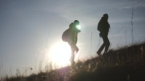 Tourists with backpacks at sunset travel through the mountains. The concept of a healthy lifestyle. stock video