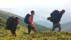 Tourists with backpacks walking on trek.