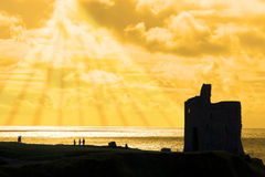 Tourists at ballybunion castle at sunset. Old castle in Ballybunion county Kerry Ireland at sunset with tourists and sun rays in background Royalty Free Stock Image