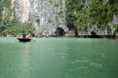 Tourists on bamboo boats touring around the islands and caves of ha long bay. Vietnam Royalty Free Stock Photos