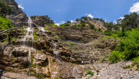 Tourists at the base of the waterfall Uchan-Su, Republic of Crimea Royalty Free Stock Photography
