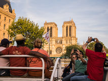 Tourists on bateaux mouches take pictures of Notre Dame, Paris,. Tourists on a tour boat on the Seine photograph Notre Dame cathedral, in Paris, France Royalty Free Stock Image