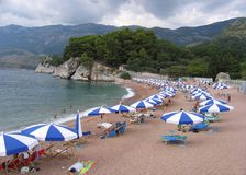Tourists at the beach. With parasols, in Sveti Stefan, Montenegro Royalty Free Stock Photo
