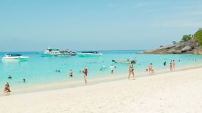 Tourists on the beach on a background of the many boats of different sizes. SIMILANS, THAILAND - CIRCA MAR 2014: Tourists on the beach on a background of the stock footage