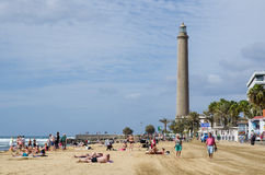 Tourists at the beach by the Maspalomas lighthouse in Spain Royalty Free Stock Photos