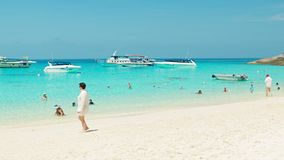 Tourists on the beach with white sand. Speedboats waiting at anchor Stock Images