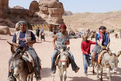 Tourists with Bedouins visiting the ancient ruins of Petra on donkeys, Jordan Royalty Free Stock Photo